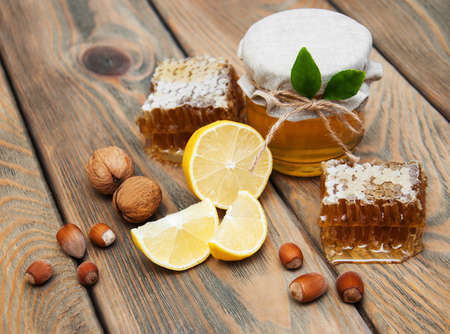 curative: honey and lemon on a old wooden background Stock Photo