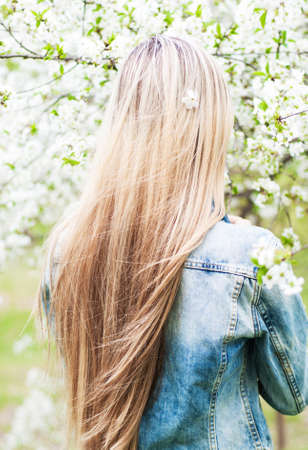 young girl with beautiful long hair in the spring garden