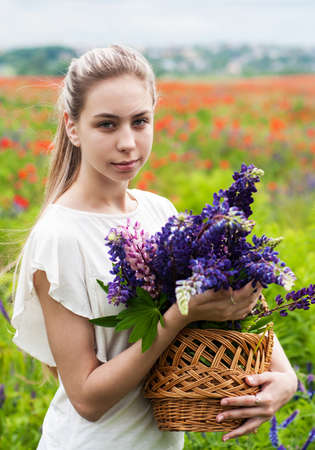 beautiful girl with basket of lupine flowers in hands Stock Photo