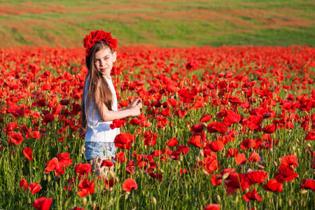 Beautiful girl in the field with red poppy flowers Stock Photo