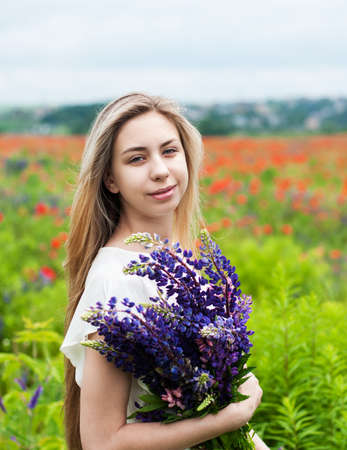 beautiful girl with bouquet of lupine flowers in hands Stock Photo