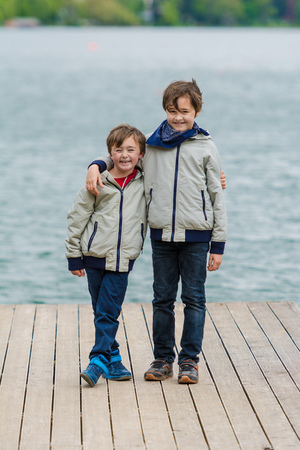 wooden dock: Young boys standing on a wooden dock of the lake