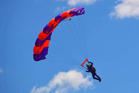 parachute jump: Colorful parachute against blue sky and white feathery clouds. Parachuting freefall in blue sky Stock Photo
