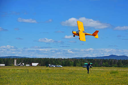 airplane performing a demonstration low over the ground. There is a video of the plane during a speech. Stunt plane in the air