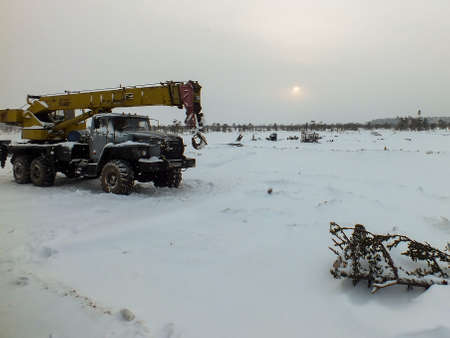 Mobile crane in the snow-covered field Banco de Imagens - 88696293