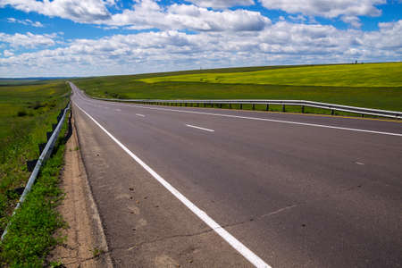 The asphalt road in summer prairies under blue sky with white clouds
