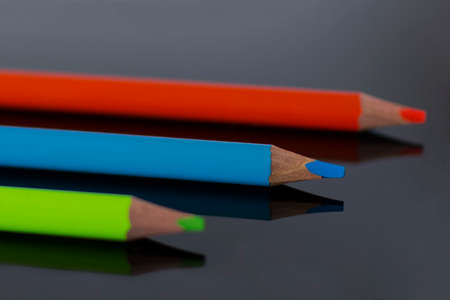 Multicolor pencils lie with reflection on black plexiglass Reklamní fotografie