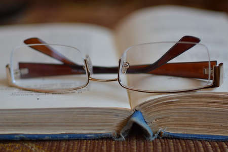 glasses lying on an open book Stock Photo