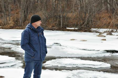 A man looks at winter river Фото со стока