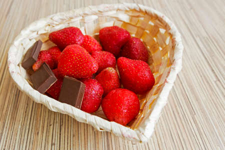 Delicious ripe strawberry and chocolate in wooden basket