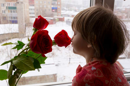 Cute little girl sniffing the scent of a rose.