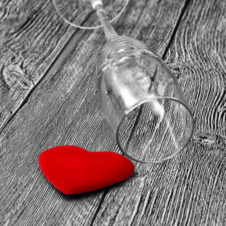 The concept of harm of alcohol to health and family. Black and white background, red heart and empty wine glass. Stok Fotoğraf