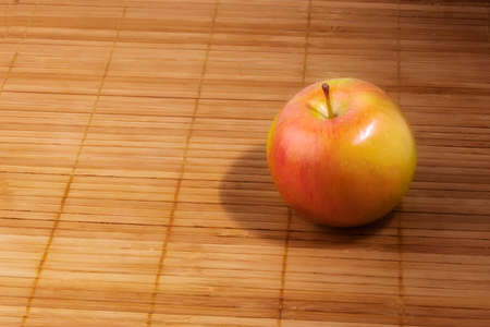 Ripe apple on wooden napkin, side view. The concept of vegetarianism, healthy food. Stok Fotoğraf