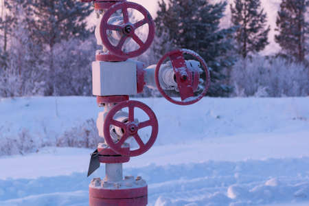 Gas or oil valve covered with snow. Oil pump jack in work. Latch on a oil well Stock Photo