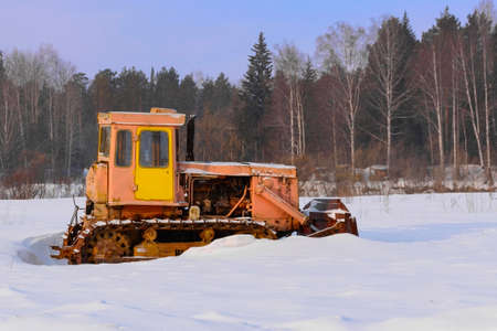 Concept of frosty and snowy winter. Old rusty tractor in the snow. A tractor sitting in a snowy field. 版權商用圖片