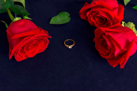Red roses and golden ring on the dark background.Valentines day, wedding or birthday concept