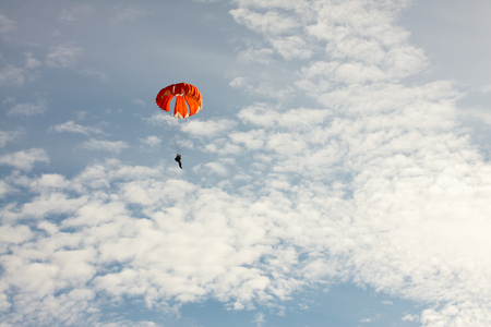 Red-orange parachute on background blue sky with clouds. Stock Photo