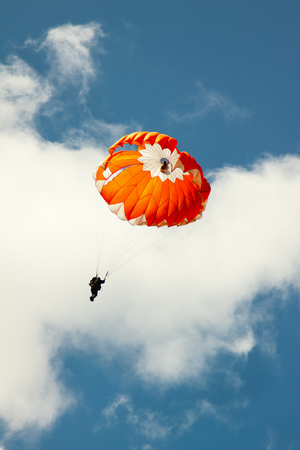 Red parachute on background blue sky with clouds.