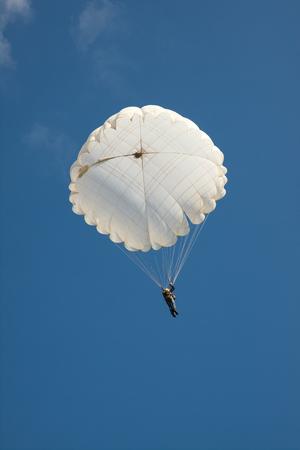 White round parachute on background blue sky. Stock Photo