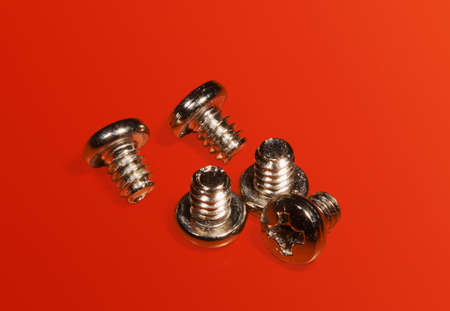 Screws for assembly of a computer on a red table