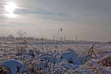 Field about the big city in the winter with sun and snow photo