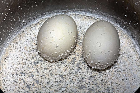 Hard-boiled eggs with the remnants of salt in a saucepan Stock Photo