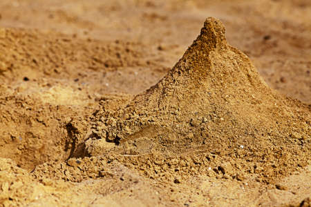 A pyramid of sand in the childrens sandbox