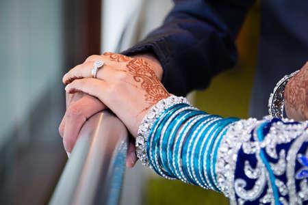 asian bride: Brides hands grooms hands