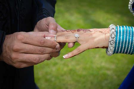 jewellry: Groom putting ring on