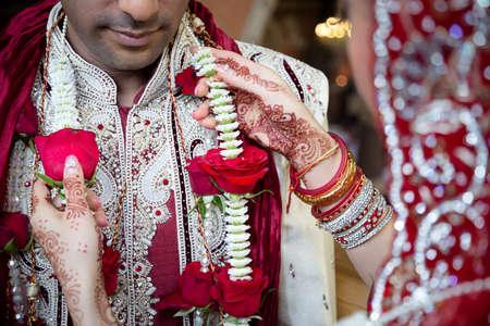 Bride adjusting grooms garland