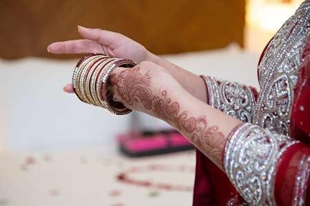 bangles hand: Bride putting on her wedding bangles