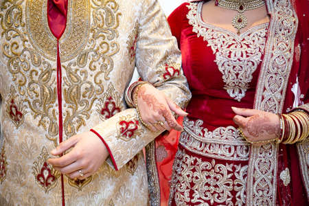 outdoor wedding: Asian bride and groom arm in arm