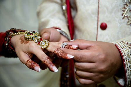 asian bride: groom putting brides ring on