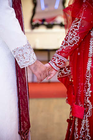 bride dress: bride and groom holding hands indian