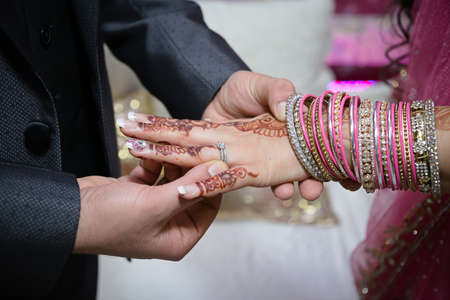 bangles hand: groom putting ring on indian bride wearing pink Stock Photo