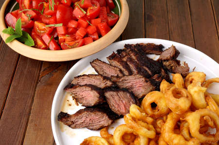 flank: Flank steak with fries onion rings and salad Stock Photo