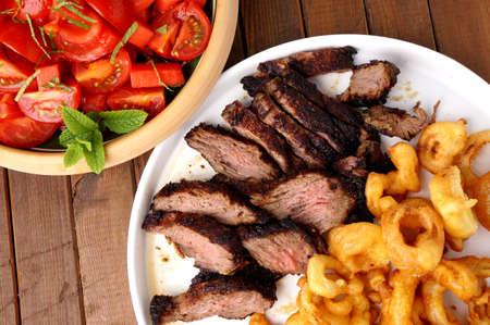 Flank Steak mit Pommes Zwiebelringen und Salat Standard-Bild - 30148308