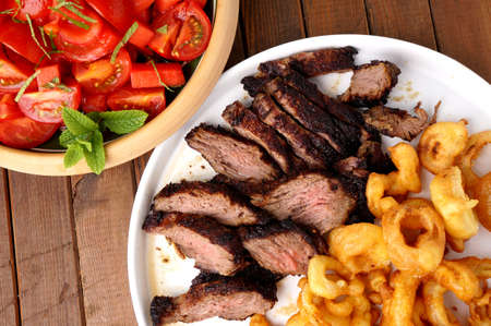Flank steak with fries onion rings and salad Stock Photo
