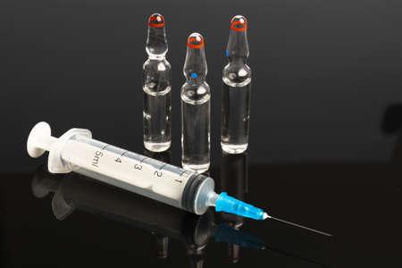 Ampules and syringe isolated on black background photo