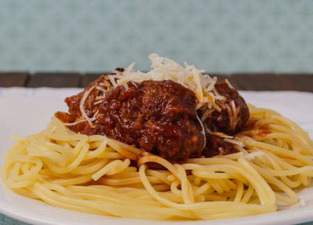 Pasta and meatballs served with parmesan cheese photo