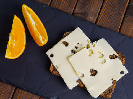 wholemeal rye bread with cheese and orange slice photo