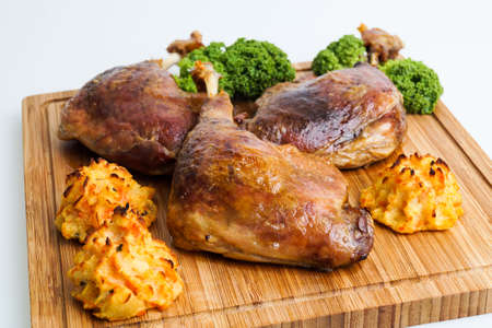 crispy duck leg served with baked potatoes photo