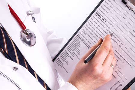 Male doctor fills patient registration form prior to admission and examination