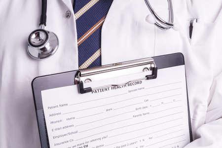 enfermedades del corazon: Doctor de sexo masculino se llena el formulario de inscripci�n del paciente antes de la admisi�n y el examen. El m�dico es completo en completar correctamente por lo que el paciente reciba el tratamiento �ptimo durante su examen y la enfermedad Foto de archivo