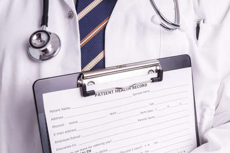 a disease: Male doctor fills patient registration form prior to admission and examination. The doctor is thorough in completing properly so the patient gets the optimal treatment during his examination and illness
