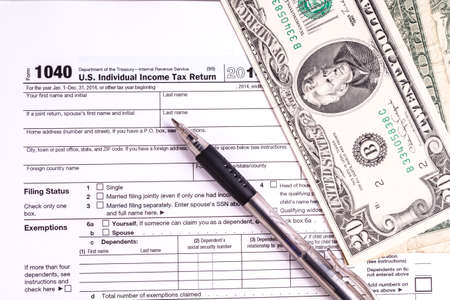 federal tax return: Tax form and Money. Filling the forms and hoping for a tax refund return