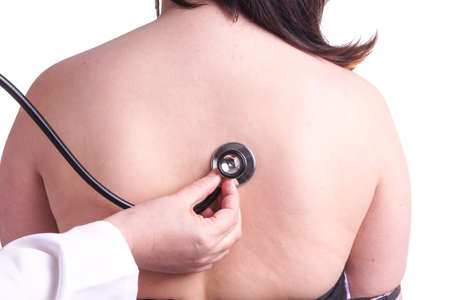 investigated: Young woman being investigated for pneumonia by her family doctor . Isolated on white. The picture shows her bare back , doctors hand and stethoscope Stock Photo