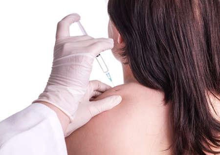inyeccion intramuscular: La mujer joven consigue inyección en la parte superior del hombro - cuello. Ella tiene rigidez en el cuello y obtiene un bloqueo. Aislado en blanco. La imagen muestra el cuello, la mano del médico y la jeringa Foto de archivo