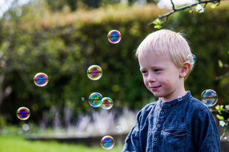 A Little boy blows soap bubbles in the garden on a summer day. He wears a blue shirt and is happy photo