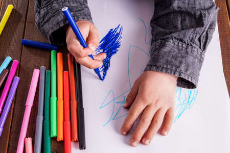assiduous: Little boy draws a drawing. He has many markers and are very focused on what he is doing Stock Photo